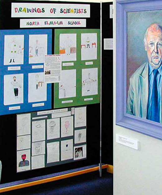 Scientist portrait alongside children's drawings in the exhibition